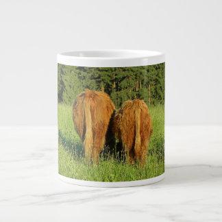 Dos partes posteriores del ganado de la montaña en taza de café grande