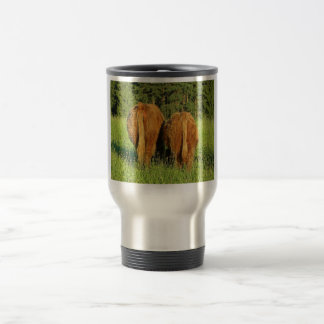 Dos partes posteriores del ganado de la montaña en taza de viaje