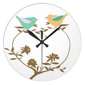 Dos pequeños pájaros en una rama en forma de reloj redondo grande