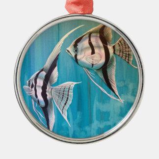 Dos pescados del ángel con de plata y negro y el adorno navideño redondo de metal