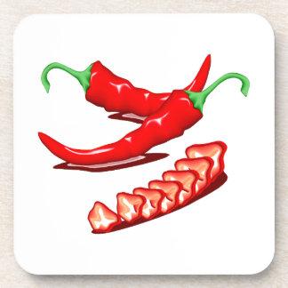 Dos pimientas de chile rojo una cortadas también posavasos de bebida