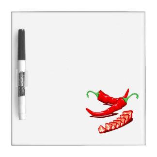 Dos pimientas de chile rojo una cortadas también tableros blancos