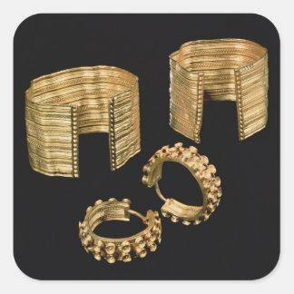 Dos pulseras talladas abiertas y un par de calcomanías cuadradas