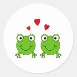 Dos ranas verdes con los corazones rojos etiqueta redonda