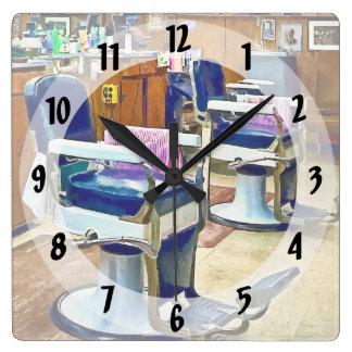Dos sillas de peluquero con los cabos rayados reloj cuadrado