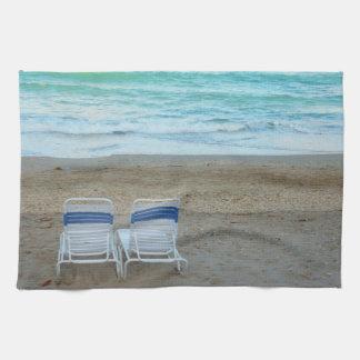Dos sillas en olas oceánicas de la arena de la pla toallas de cocina