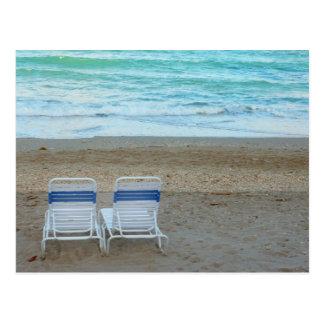 Dos sillas en olas oceánicas de la arena de la postal