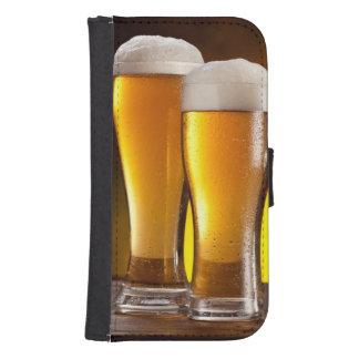 Dos vidrios de cervezas en una tabla de madera billeteras para teléfono