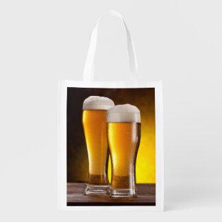 Dos vidrios de cervezas en una tabla de madera bolsas de la compra