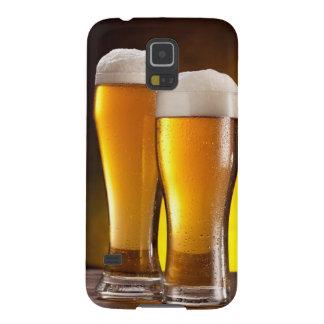 Dos vidrios de cervezas en una tabla de madera fundas de galaxy s5