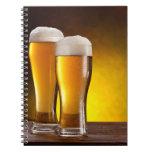 Dos vidrios de cervezas en una tabla de madera libro de apuntes con espiral