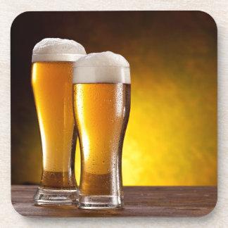 Dos vidrios de cervezas en una tabla de madera posavasos de bebidas