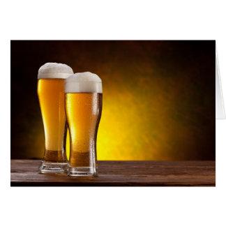Dos vidrios de cervezas en una tabla de madera tarjeta de felicitación