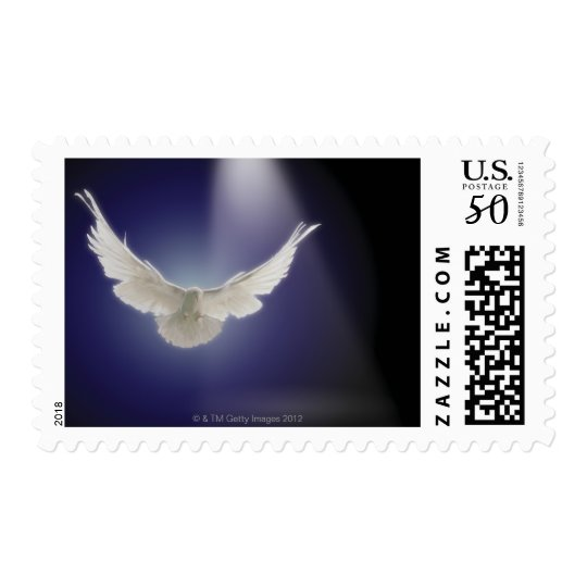 Dove flying through beam of light postage