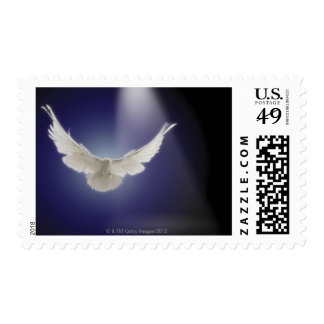 Dove flying through beam of light postage