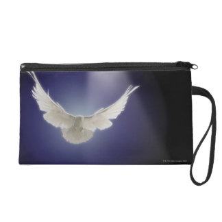 Dove flying through beam of light wristlet clutches