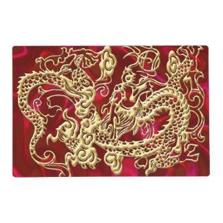 Dragón grabado en relieve del oro en el satén rojo salvamanteles