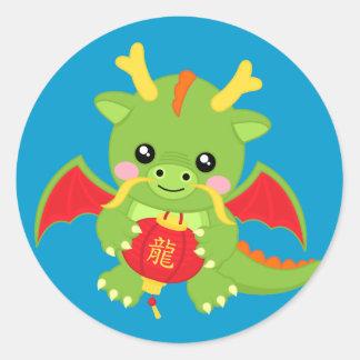 Dragón que sostiene la linterna pegatina redonda