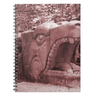 dragon statue mouth open stone faded reddish notebook