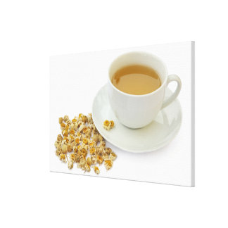 Dried camomile flowers beside a cup of camomile stretched canvas prints