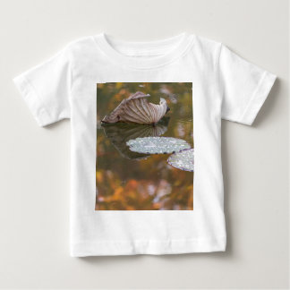 dried waterlily and reflection on lake in autumn baby T-Shirt