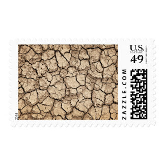 Dry cracked ground during drought postage