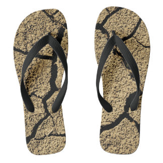 Dry land with cracked earth in drought flip flops