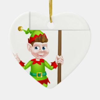 Duende del navidad que lleva a cabo la muestra adorno navideño de cerámica en forma de corazón