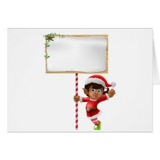 Duende del navidad que lleva a cabo una muestra tarjeta de felicitación