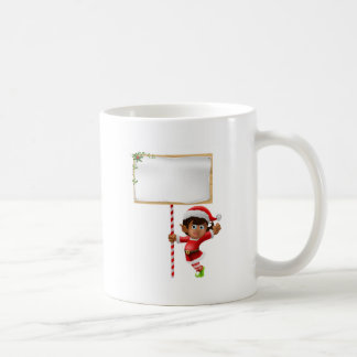 Duende del navidad que lleva a cabo una muestra tazas