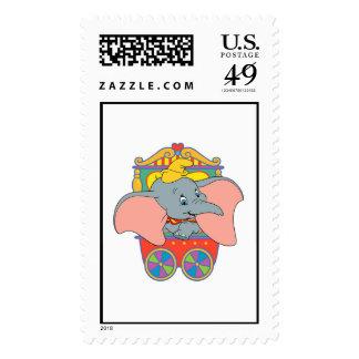 Dumbo que se sienta en su carretilla timbre postal