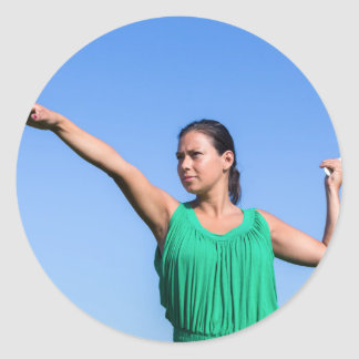 Dutch woman throwing boomerang in blue sky classic round sticker