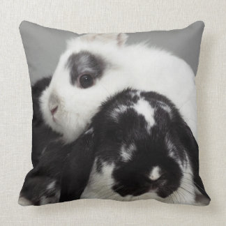 Dwarf-eared rabbit leaning over lop-eared throw pillow