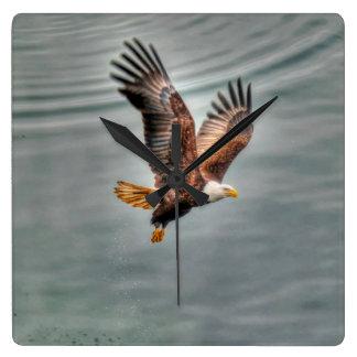 Eagle calvo americano que vuela sobre el océano reloj cuadrado