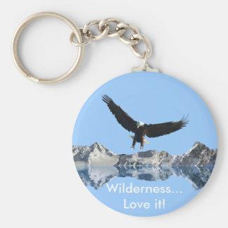 Eagle calvo que vuela y montañas llaveros