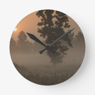 Early morning, rising sun and ground fog round clock