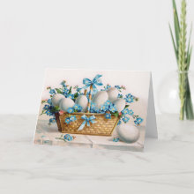 Easter Basket Card - A beautiful wicker basket filled with white eggs and surrounded by the brightest blue little flowers with a few pink ones here and there. The blue ribbon matches the flowers perfectly. This type of Victorian print was popular in the early 1900's.