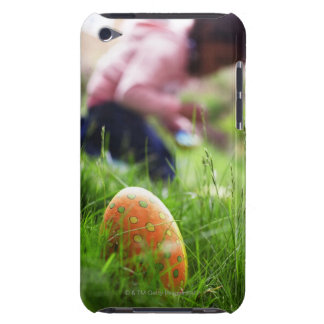 Easter eggs hidden in grass, girl (7-9) in iPod touch cover