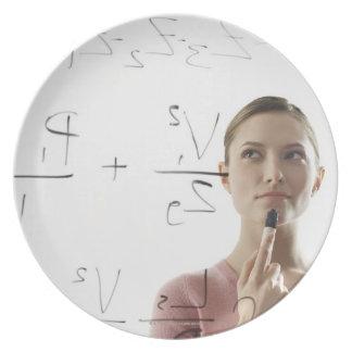Ecuaciones calculadoras de la mujer joven sobre el plato de cena
