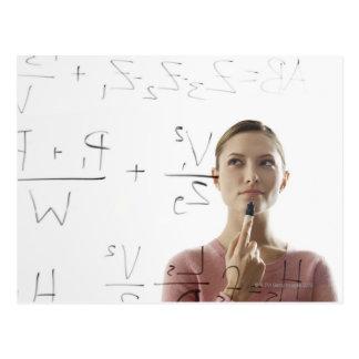Ecuaciones calculadoras de la mujer joven sobre el postal