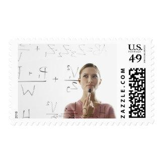 Ecuaciones calculadoras de la mujer joven sobre el timbre postal