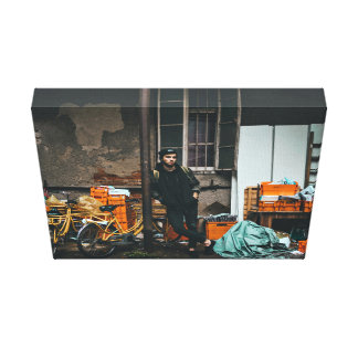 Edgy young man stands outside factory canvas print