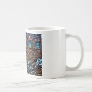 Edificio de ladrillo abandonado de la pintada taza de café