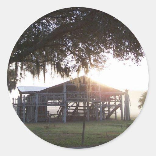 Edificio viejo del rancho debajo de árboles con la pegatina redonda