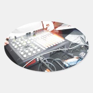 EDM DJ mixing music at an underground show Oval Sticker