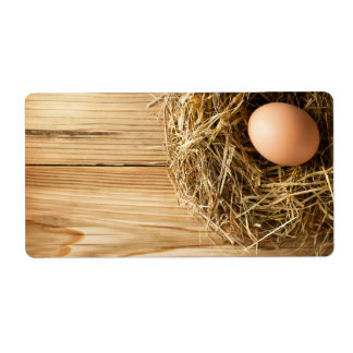 Egg In Hay Nest On Wooden Table Background Label