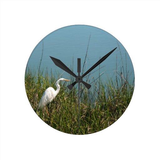 Egret blanco que se coloca en agua de la hierba w reloj de pared