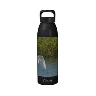 Egret blanco que vuela sobre hierba del agua botella de beber