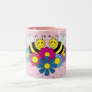 Ejemplo del diseño de las abejas y de las flores taza dos tonos