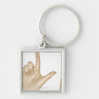 Ejemplo del lenguaje de signos usando los dedos y llavero cuadrado plateado